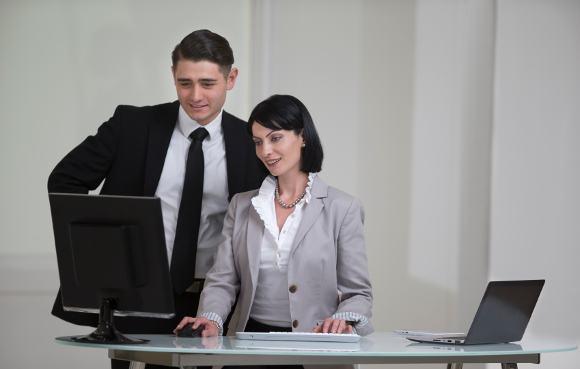 นักธุรกิจสองคนยืนอยู่ข้างหลังโต๊ะทำงาน
