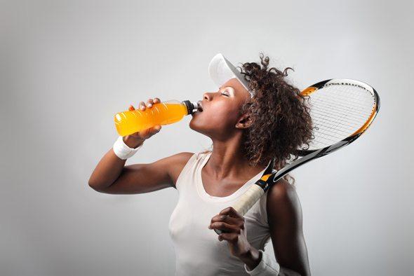 หญิงแอฟริกันถือไม้เทนนิสดื่มเครื่องดื่มกีฬา