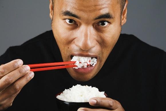 ผู้ชายเอเชียกำลังกินข้าว 580 พิกเซล