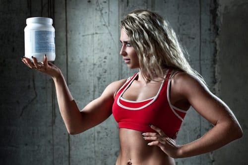 นักกีฬาหญิงถือภาชนะที่มีโปรตีน