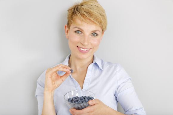 ผู้หญิงผมบลอนด์กำลังกินบลูเบอร์รี่