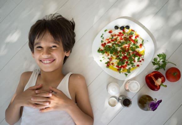 เด็กชายยิ้มกับอาหารเมดิเตอร์เรเนียน