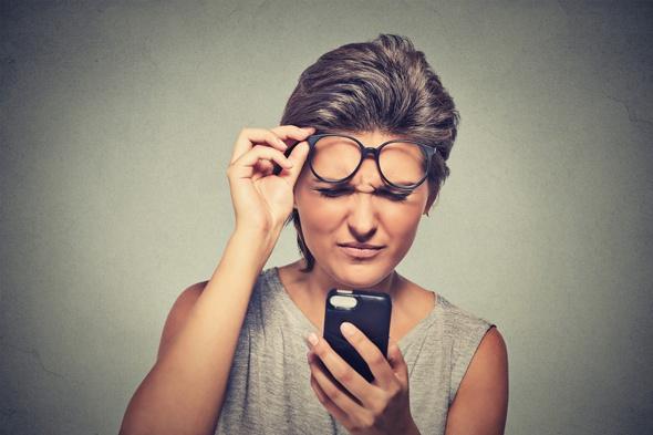 ผมสีน้ำตาลกับแว่นตามีปัญหาในการอ่านโทรศัพท์มือถือของเธอ