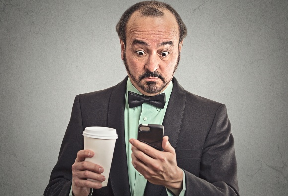 นักธุรกิจกำลังดื่มกาแฟมองไปที่โทรศัพท์