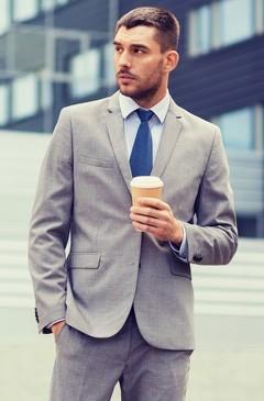 นักธุรกิจยืนอยู่ข้างนอกพร้อมถ้วยกาแฟ