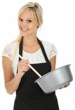 หญิงในผ้ากันเปื้อนพร้อมชามและช้อนทำอาหาร