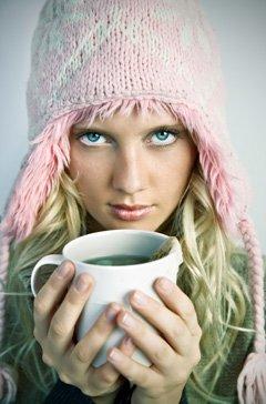 หญิงสวมหมวกถือถ้วยชาเขียว
