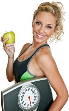 พอดีผู้หญิงถือเครื่องชั่งและแอปเปิ้ล