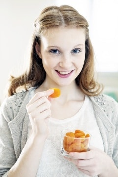 หญิงสาวกำลังรับประทานแอปริคอตแห้ง