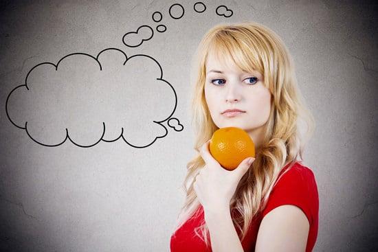 หญิงสาวถือส้มและกำลังคิด
