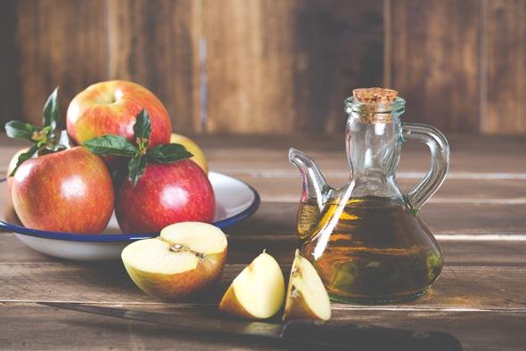เหยือกแก้วของน้ำส้มสายชูแอปเปิ้ลไซเดอร์และจานที่มีแอปเปิ้ลอยู่