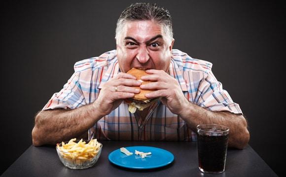 ชายที่โลภและมีน้ำหนักเกินกำลังรับประทานอาหารขยะ