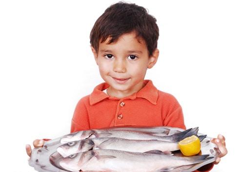 เด็กชายตัวเล็กถือปลา