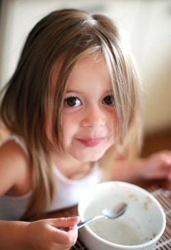 เด็กหญิงตัวเล็ก ๆ กำลังรับประทานอาหารเช้า