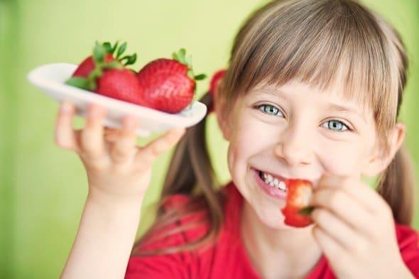 เด็กหญิงตัวเล็ก ๆ กำลังกินสตรอเบอร์รี่