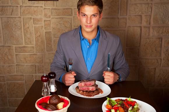ผู้ชายที่ร้านอาหารกำลังกินสเต็ก
