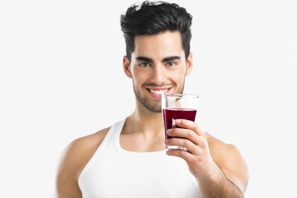 ผู้ชายถือแก้วน้ำผลไม้