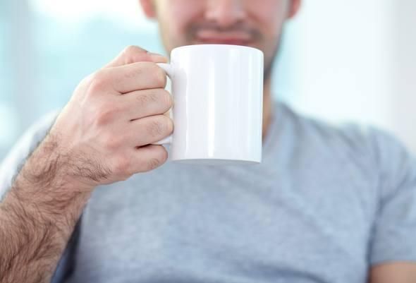 ผู้ชายถือแก้วกาแฟสีขาว