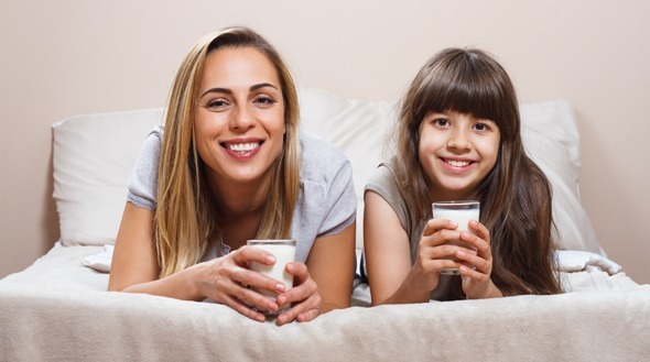 แม่และลูกสาวดื่มนมบนเตียง