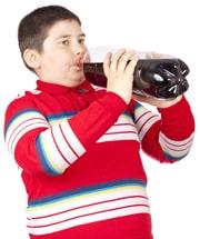 เด็กชายน้ำหนักเกินกำลังดื่มโซดาจากขวด