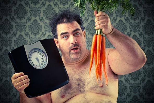 ผู้ชายที่มีน้ำหนักเกินพร้อมเครื่องชั่งและแครอท