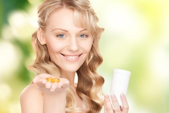 ผู้หญิงยิ้มถือโอเมก้า 3 แคปซูล