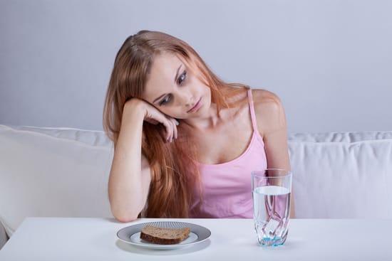 หญิงสาวที่หิวโหยมองไปที่ขนมปังปิ้ง