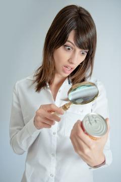 ผู้หญิงประหลาดใจกำลังตรวจสอบฉลากอาหาร