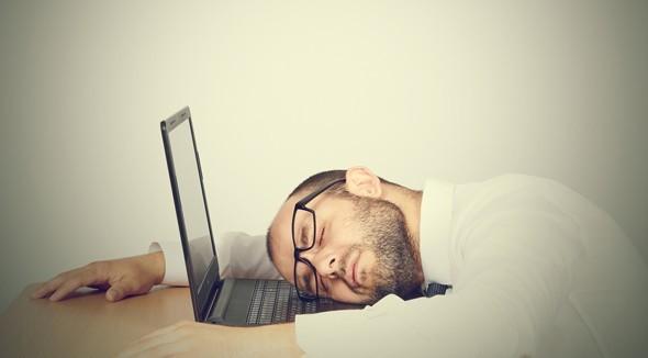 ผู้ชายที่เหนื่อยล้านอนเอาหัวลงบนแล็ปท็อป