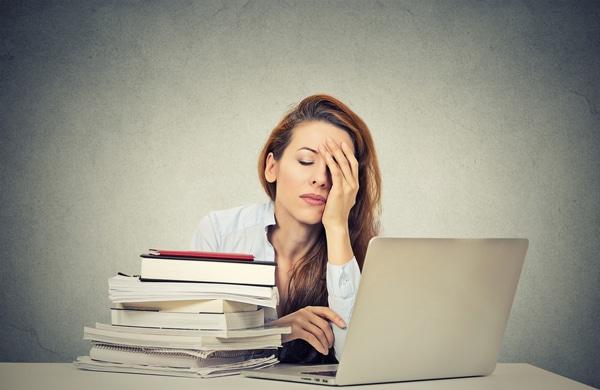 ผู้หญิงที่เหนื่อยล้านั่งอยู่ที่โต๊ะทำงานของเธอ