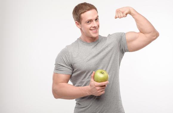 ผู้ชายที่แข็งแรงมากกำลังดิ้นจับแอปเปิ้ล