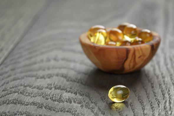 แคปซูลวิตามินดีในชามไม้ขนาดเล็ก
