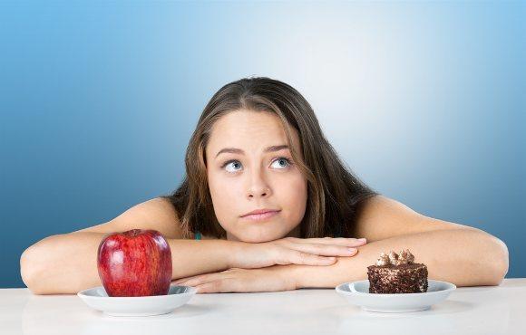 ผู้หญิงกำลังตัดสินใจระหว่างแอปเปิ้ลกับเค้ก