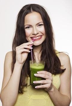 ผู้หญิงกำลังดื่มสมูทตี้สีเขียวด้วยฟาง