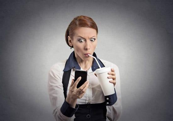 ผู้หญิงกำลังดื่มโซดาขณะดูโทรศัพท์
