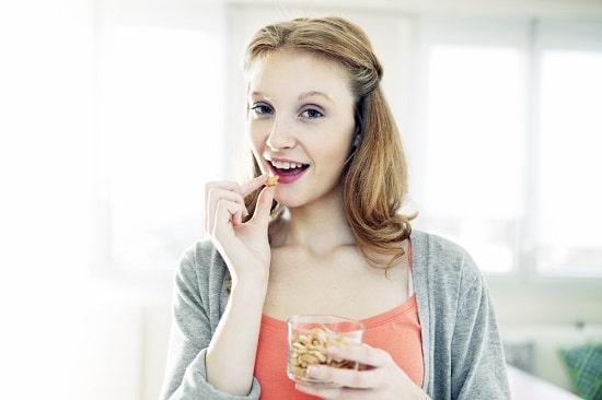 ผู้หญิงกำลังกินถั่วจากแก้ว