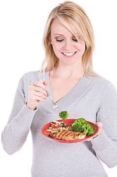 ผู้หญิงกินปลาแซลมอนและบร็อคโคลี