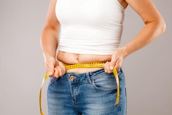 ผู้หญิงรับน้ำหนักและวัดหน้าท้อง