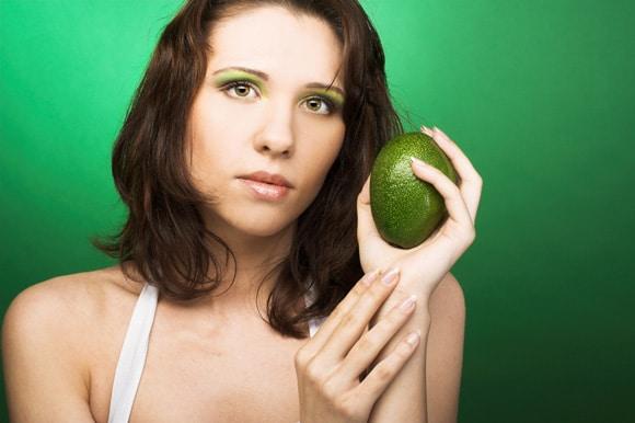 ผู้หญิงถืออะโวคาโดสีเขียว