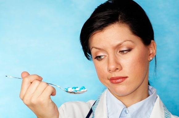 ผู้หญิงถือช้อนที่เต็มไปด้วยยา