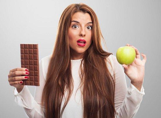 ผู้หญิงถือช็อกโกแลตและแอปเปิ้ล