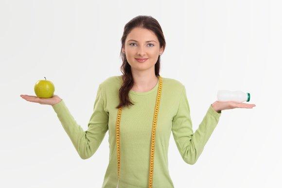 ผู้หญิงถือโปรไบโอติกและแอปเปิ้ล