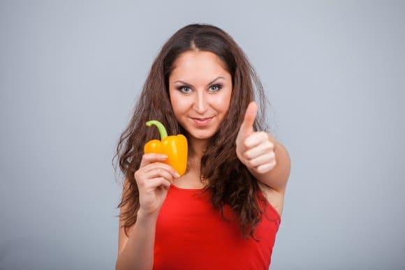 ผู้หญิงถือพริกไทยเหลืองยกนิ้วให้
