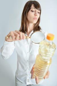 ผู้หญิงกำลังตรวจสอบขวดน้ำมันด้วยแว่นขยาย