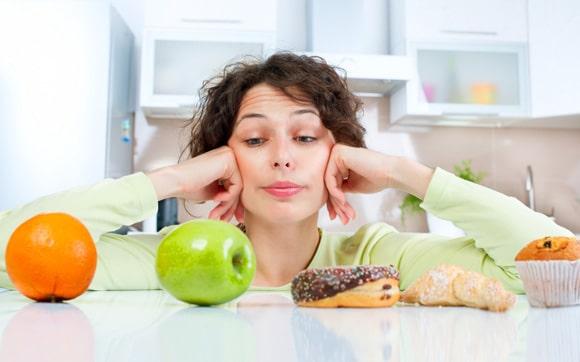 ผู้หญิงกำลังเลือกระหว่างผลไม้กับอาหารขยะ