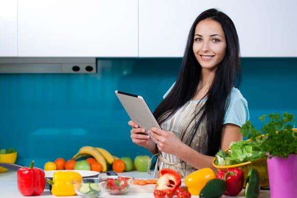 ผู้หญิงใช้แท็บเล็ตในครัวพร้อมผักและผลไม้