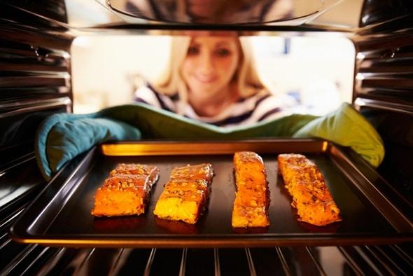 ผู้หญิงใส่เนื้อปลาแซลมอนในเตาอบ