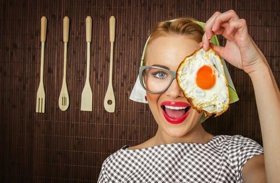 ผู้หญิงยิ้มและถือไข่ดาว