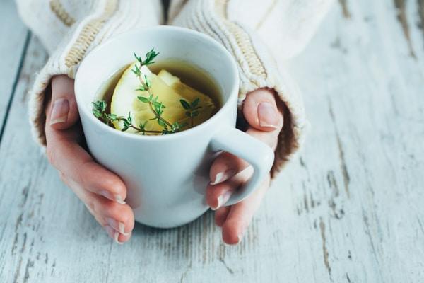 ผู้หญิงกำลังอุ่นมือกับถ้วยชา