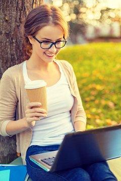 ผู้หญิงกำลังอ่านกาแฟบนแล็ปท็อป